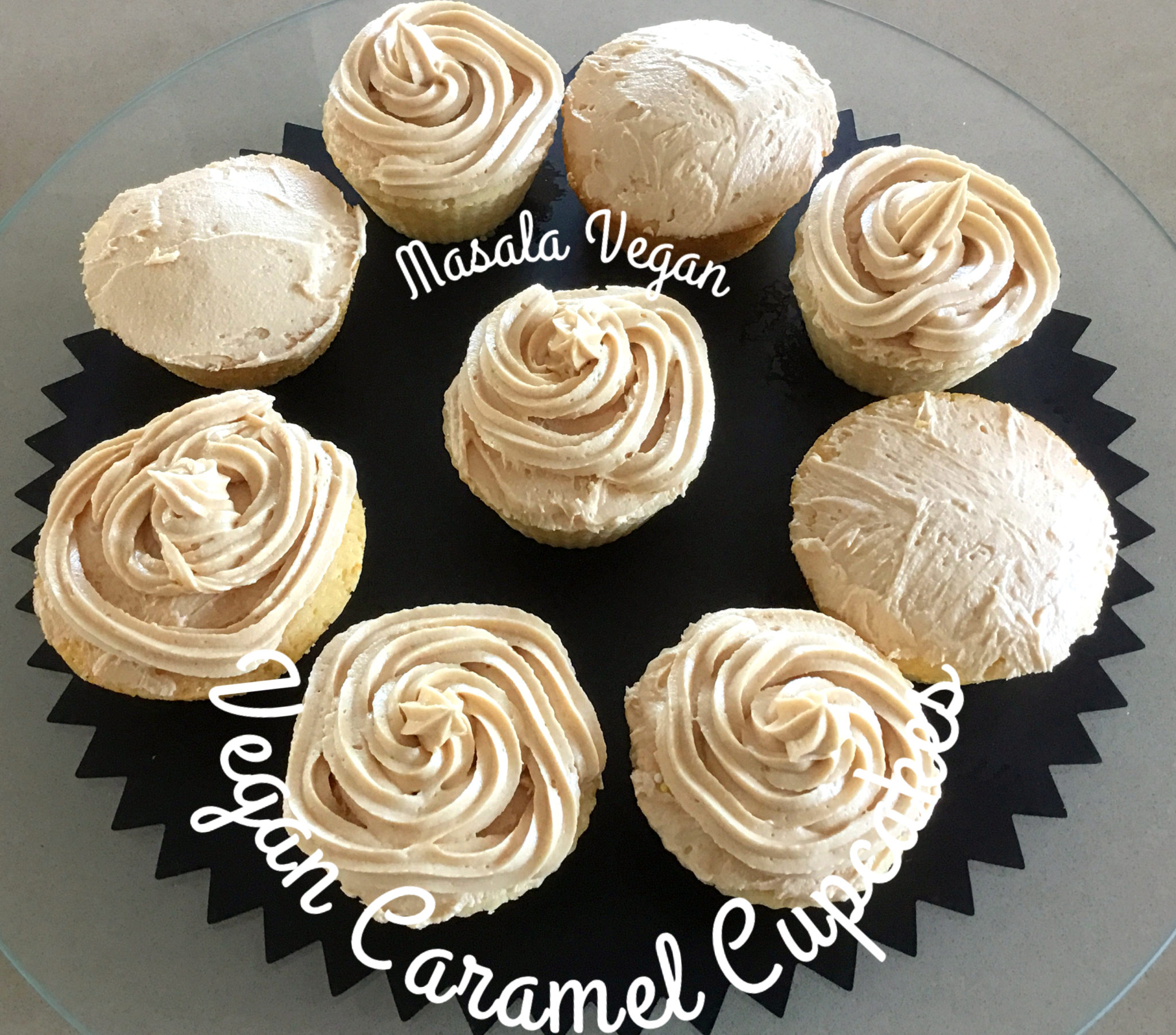 9 vegan caramel cupcakes with icing on a black plate