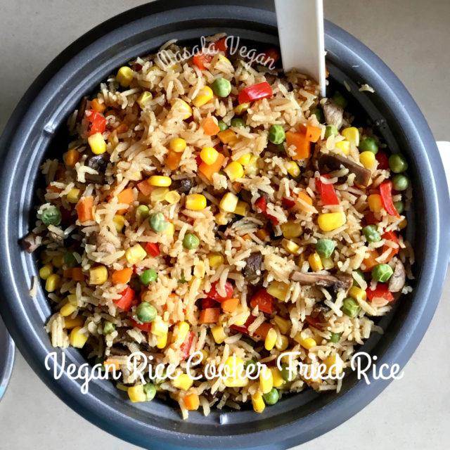 Grey rice cooker pot with fried rice showing brown basmati rice with carrot, corn, red capsicum pieces and green shallots