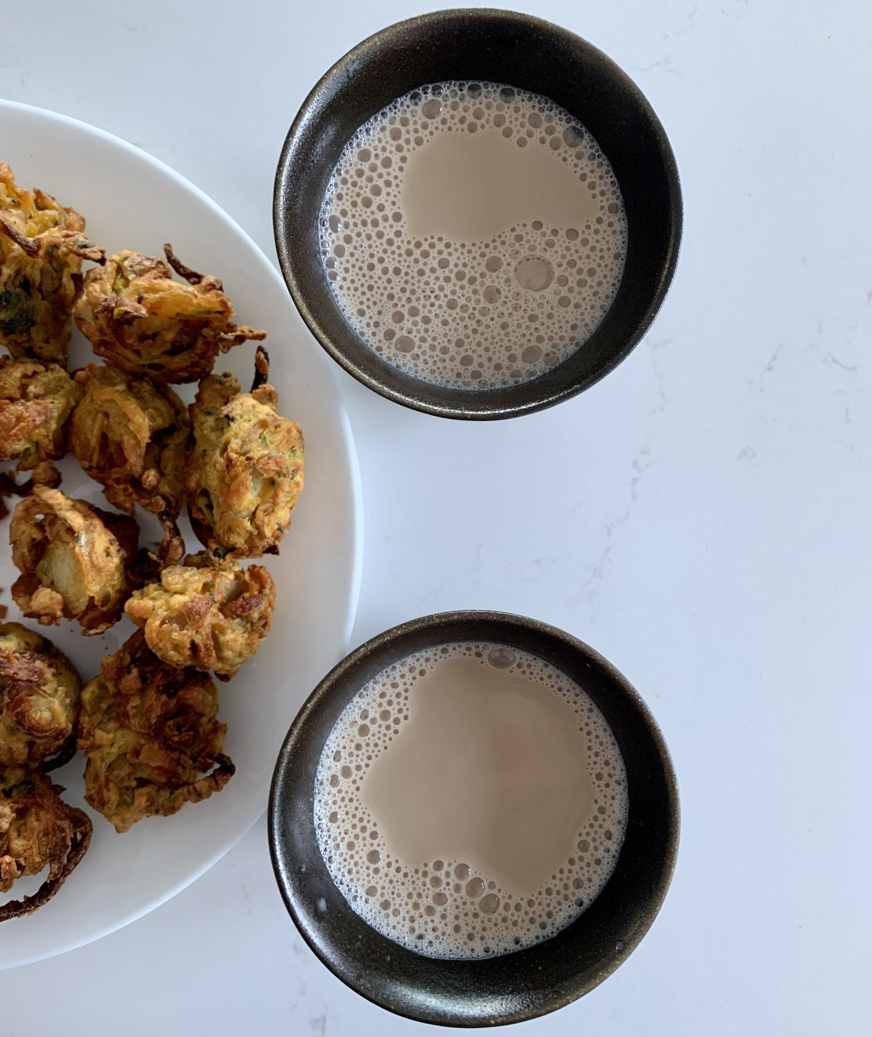 Two black mugs with vegan milky chai and half a white -late with pakora