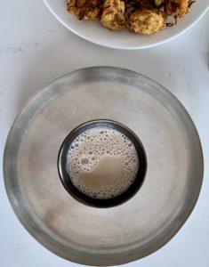 A black mug with vegan milky chai on a round silver plate